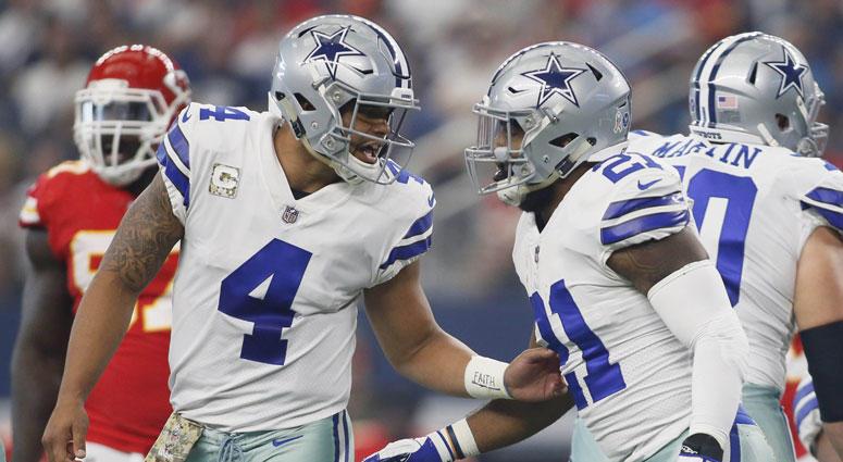 Dallas Cowboys quarterback Dak Prescott (4) tells running back Ezekiel Elliott