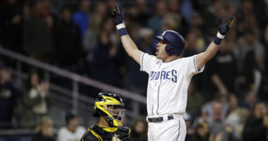 San Diego Padres' Ian Kinsler celebrates after hitting a three-run home run, next to Pittsburgh Pirates catcher Elias Diaz during the sixth inning of a baseball game Thursday, May 16, 2019, in San Diego