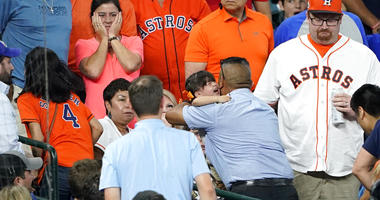 A young child is carried from the stands after being injured by a foul ball off the bat of Chicago Cubs' Albert Almora Jr.