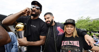 Toronto Raptors forward Kawhi Leonard, left to right, smokes a cigar holding his playoffs MVP trophy as he celebrates with performing artist Drake and his mother Kim Robertson during the 2019 Toronto Raptors NBA basketball championship parade in Toronto,