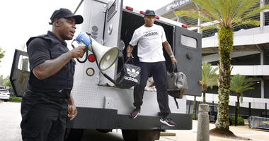 Comedian Ha Ha Davis, left, announces the arrival of Jacksonville Jaguars cornerback Jalen Ramsey to NFL football training camp as he steps from the back of an armored car outside TIAA Bank Field in Jacksonville, Fla., Wednesday, July 24, 2019.