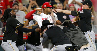 Cincinnati Reds relief pitcher Amir Garrett (50) looks to throw a punch as he is held back by a number of Pittsburgh Pirates players during a brawl in the ninth inning of a baseball game in Cincinnati on Tuesday, July 30, 2019.