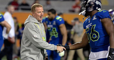 NFC coach Jason Garrett of the Dallas Cowboys shakes hands with NFC defensive end Cliff Avril of the Seattle Seahawks