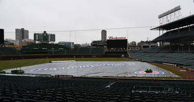 The tarp lays on Wrigley Field after a baseball game between the Atlanta Braves and the Chicago Cubs was postponed on Sunday, April 15, 2018, in Chicago.