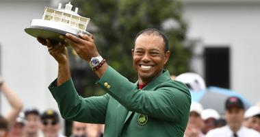 Tiger Woods celebrates with the green jacket and trophy after winning The Masters golf tournament