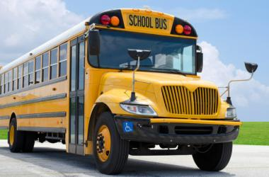 Yellow school bus on the blacktop on a beautiful sunny day