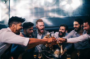 Dudes cheering beers at a bachelor party