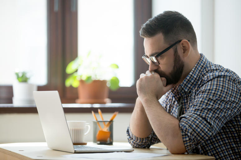 Man looks contemplative about what he sees on computer screen