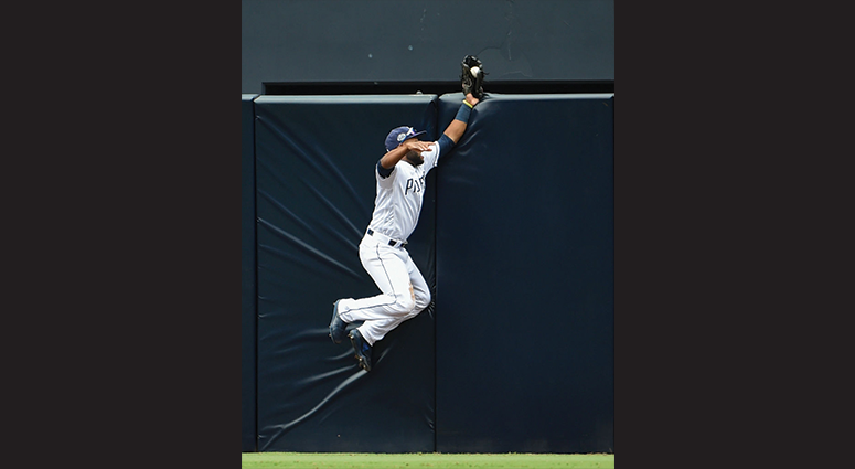 Manuel Margot #7 of the San Diego Padres can't make the catch on a double hit by Brandon Nimmo #9 of the New York Mets during the seventh inning of a baseball game at Petco Park May 8, 2019 in San Diego, California. Margot dropped the ball after slamming