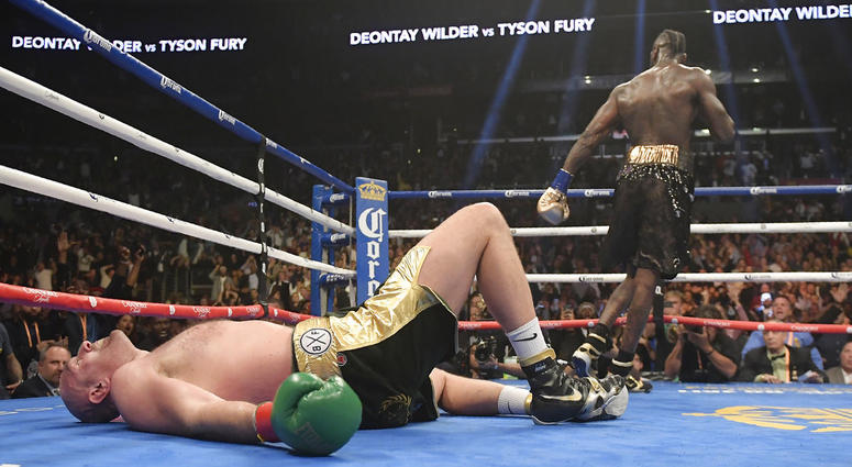 Tyson Fury, of England, lies on the canvas