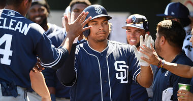 MARCH 18: Josh Naylor #87 of the San Diego Padres celebrates with teammates in the dugout after hitting a solo home run during the second inning of a spring training game against the Cleveland Indians at Goodyear Ballpark on March 18, 2019 in Goodyear, Ar