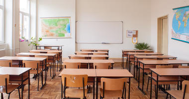 Empty classroom interior with wooden desks and chairs, maps and white board