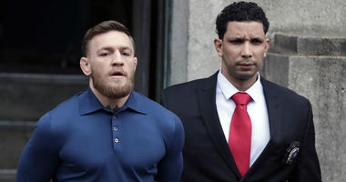 Ultimate fighting star Conor McGregor, left, is led by an official to an unmarked vehicle while leaving the 78th Precinct of the New York Police Department, Friday, April 6, 2018.