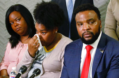 Amber Carr, center, wipes a tear as her sister, Ashley Carr, left, and attorney Lee Merritt, right, listen to their brother Adarius Carr talk about their sister, Atatiana Jefferson during a news conference.
