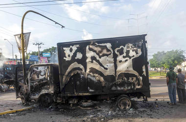 A burnt out truck used by gunmen smolders on an intersection, a day after street battles between gunmen and security forces in Culiacan, Mexico, Friday Oct. 18, 2019.