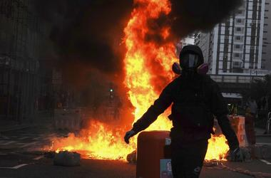 Protestors set fire on a street to prevent police from approaching in Hong Kong, Sunday, Oct. 20, 2019.
