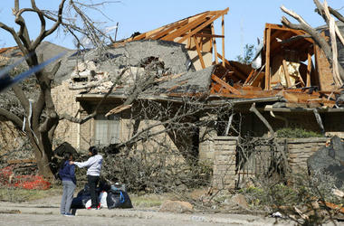 Women stand outside a house damaged by a tornado in the Preston Hollow section of Dallas.