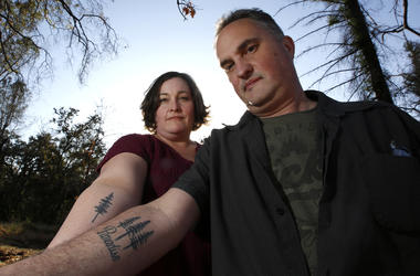 Laura and Chris Smith display their Paradise tattoos they had done to show support for their former community during a visit to Paradise, Calif.