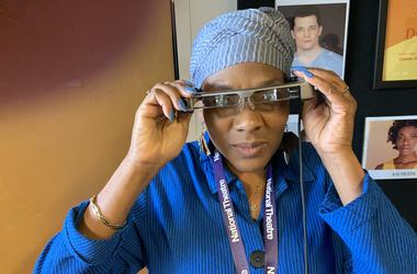 "Cheryl Johnson, West Philadelphia, who suffers from hearing loss, puts on her smart caption glasses which she described as ""amazing"" in helping her to follow the performance of ""Dot"" at People's Light in Malvern, Chester County."