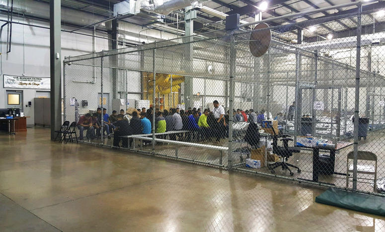 In this photo provided by U.S. Customs and Border Protection, people who've been taken into custody related to cases of illegal entry into the United States, sit in one of the cages at a facility in McAllen, Texas.