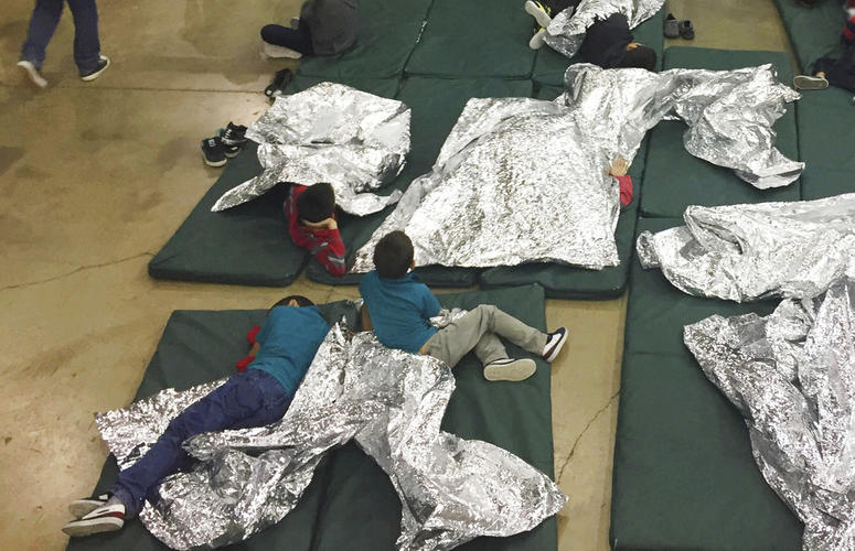 In this photo provided by U.S. Customs and Border Protection, people who've been taken into custody related to cases of illegal entry into the United States, rest in one of the cages at a facility in McAllen, Texas.