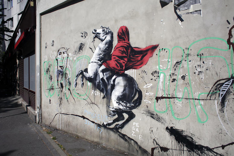 A graffiti believed to be attributed to street artist Banksy is seen on a wall along a street in Paris.