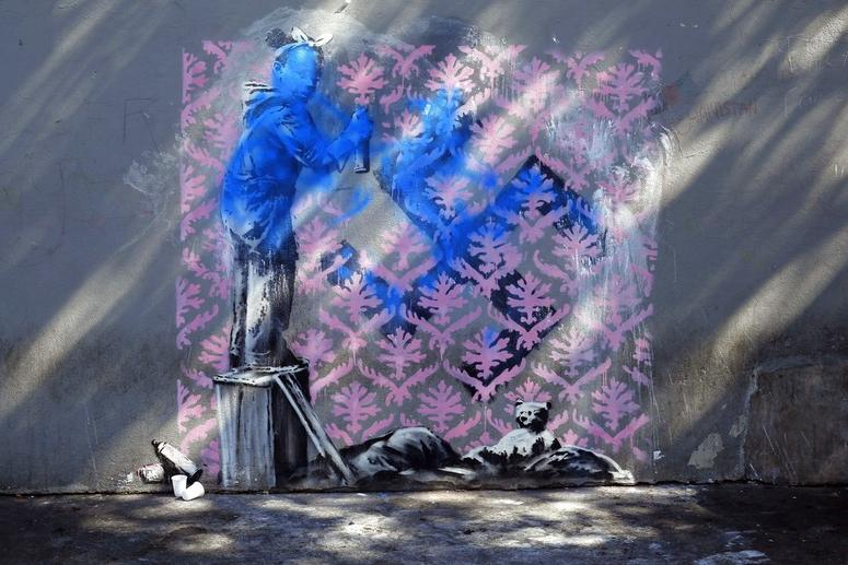 A graffiti believed to be attributed to street artist Banksy is seen on a wall in Paris.