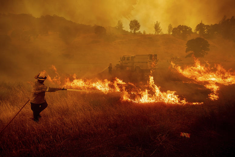A firefighter scrambles to stop a wildfire as wind drives embers across Highway 20 near Clearlake Oaks, Calif., on Sunday, July 1, 2018.
