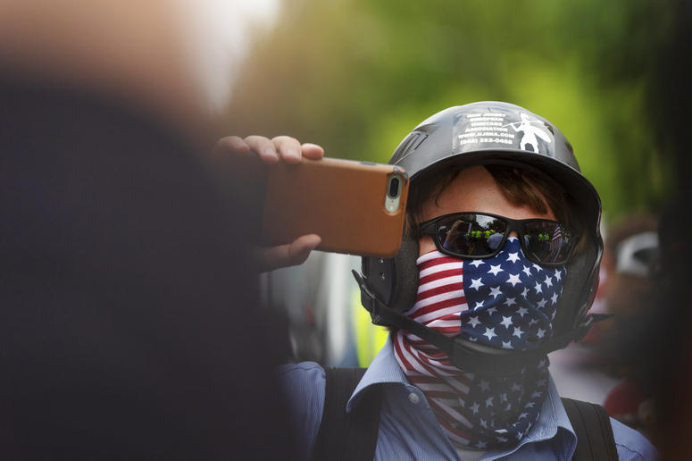 """A white nationalist holds his phone while marching to Lafayette Square during the """"Unite the Right 2"""" rally in Washington, Sunday, Aug. 12, 2018."""