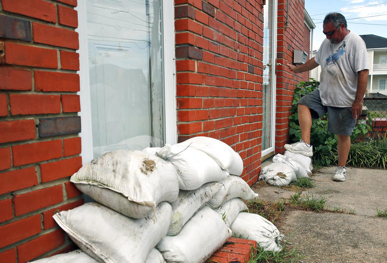 Adam Bazemore uses his foot to pack down sandbags in a doorway, Tuesday, Sept. 11, 2018, in the Willoughby Spit area of Norfolk, Va., as he makes preparations for Hurricane Florence.