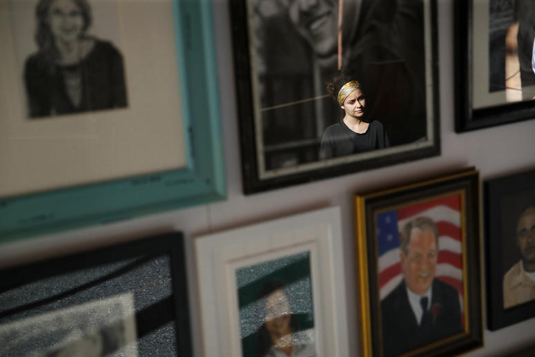 In this Sept. 25, 2018, photo, a woman looks at painted portraits of victims of the Oct. 1, 2017, mass shooting in Las Vegas on display at the Clark County Government Center in Las Vegas.