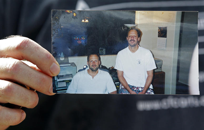In this Oct. 2, 2017 file photo, Eric Paddock holds a photo of himself, at left, and his brother, Stephen Paddock, at right, outside his home in Orlando, Fla.