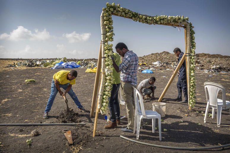 Workers erect floral installations at the scene where the Ethiopian Airlines Boeing 737 Max 8 crashed.