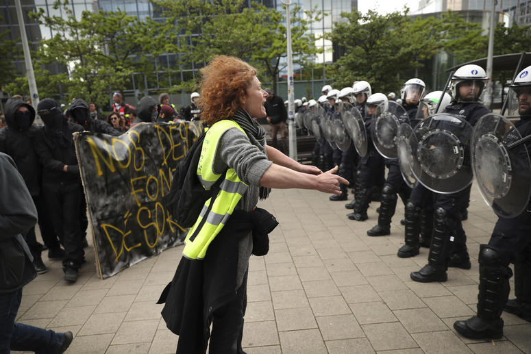 A yellow vest protestor talks to a line of police officers during a demonstration in Brussels, Sunday, May 26, 2019. The demonstration took place as Belgium took to the polls to elect regional, national and European candidates.