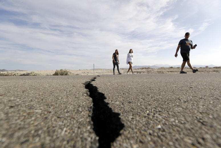 Visitors cross highway 178 next to a crack left on the road by an earthquake Sunday, July 7, 2019, near Ridgecrest, Calif.