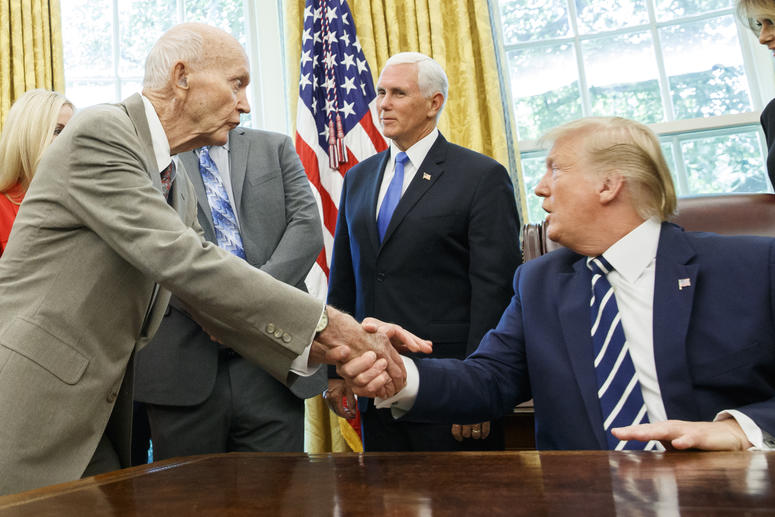 President Donald Trump shakes hands with Apollo 11 astronaut Michael Collins, left, with Vice President Mike Pence, during a photo opportunity commemorating the 50th anniversary of the Apollo 11 moon landing, in the Oval Office of the White House, Friday,