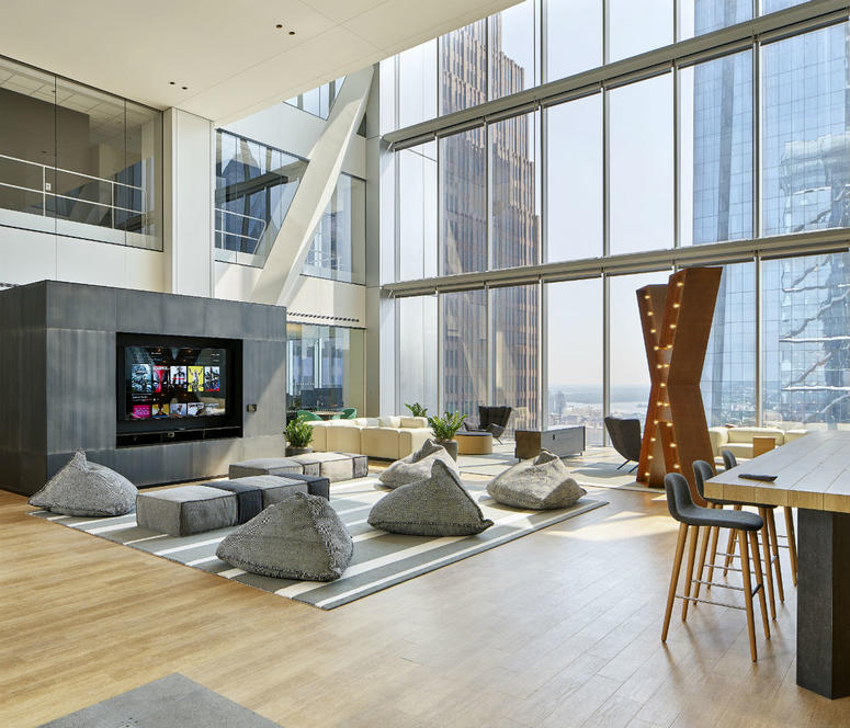 The open workspaces resemble hotel lobbies, with plush chairs and artwork surrounded by natural light.