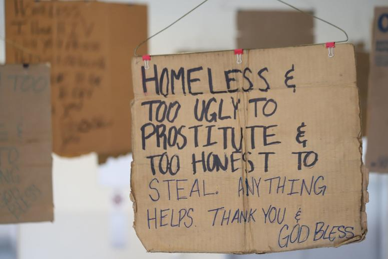 Willie Baronet, an artist and professor, purchased signs from the homeless people that they used to pander for money and turned them into a hanging art instillation.