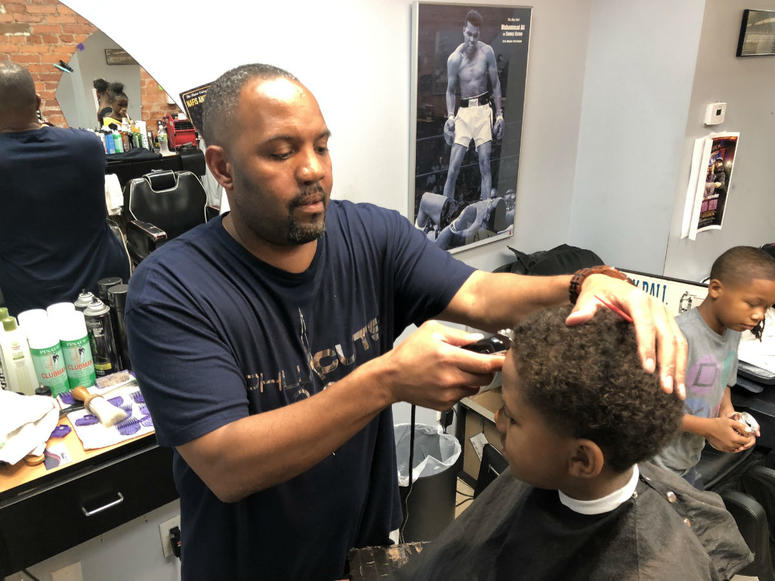Philadelphia police officers met with community members at a barbershop in West Philly.