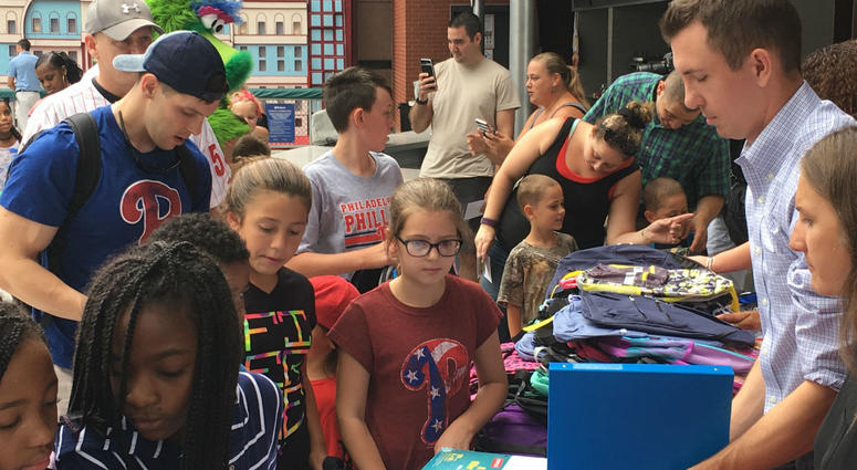 Youngsters from military families across the region line up to receive backpacks and school supplies during a special giveaway at Citzen's Bank Park on Tuesday.