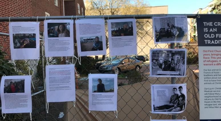 The refugee scene includes pictures and stories of real-life refugees hung on a fence nearby.