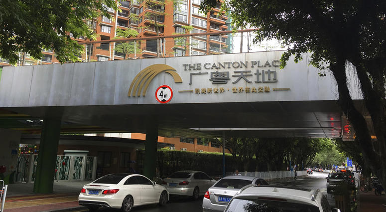 Vehicles pass by high-rise apartment buildings in The Canton Place where U.S. government workers experienced unexplained health issues in Guangzhou.