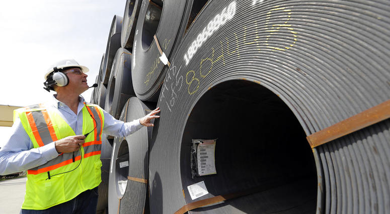 CEO Joel Johnson checks the details on a roll of steel at the Borusan Mannesmann Pipe manufacturing facility.