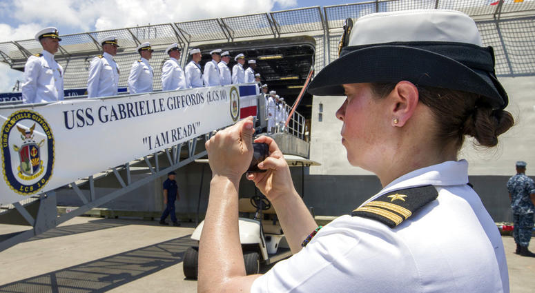 In this June 10, 2017 file photo, U.S. Navy Lt. Miranda Williams photographs sailors as they board the USS Gabrielle Giffords during a commissioning ceremony in Galveston, Texas.
