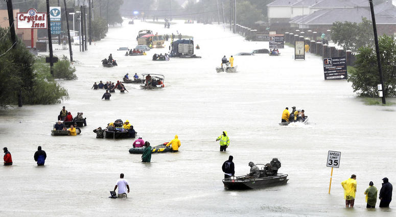 In this Aug. 28, 2017 file photo, rescue boats fill a flooded street as flood victims are evacuated as floodwaters from Tropical Storm Harvey rise in Houston.