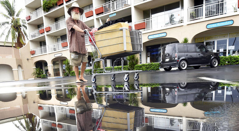 David Crocker, who is homeless, pushes his belongings past a puddle in Kihei on the Hawaiian island of Maui, Saturday, Aug. 25, 2018.