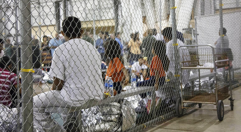 In this June 17, 2018 file photo provided by U.S. Customs and Border Protection, people who've been taken into custody related to cases of illegal entry into the United States, sit in one of the cages at a facility in McAllen, Texas.