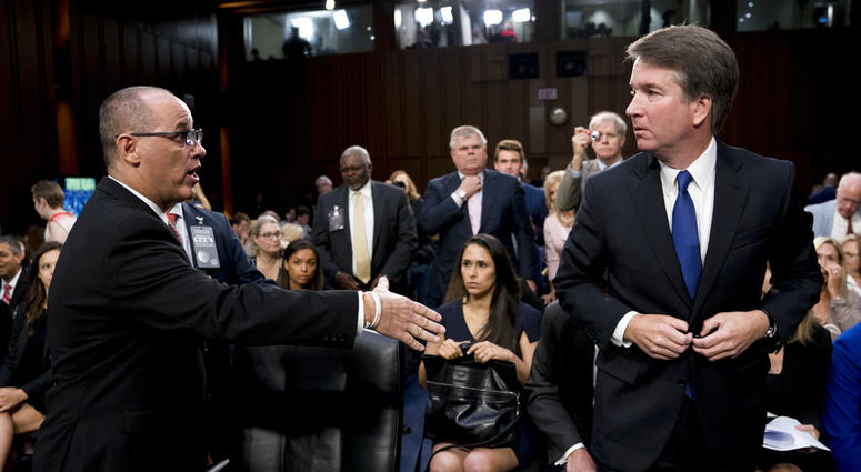 Fred Guttenberg, the father of Jamie Guttenberg who was killed in the Stoneman Douglas High School shooting in Parkland, Fla., left, attempts to shake hands with Brett Kavanaugh, right, as he leaves for a lunch break.