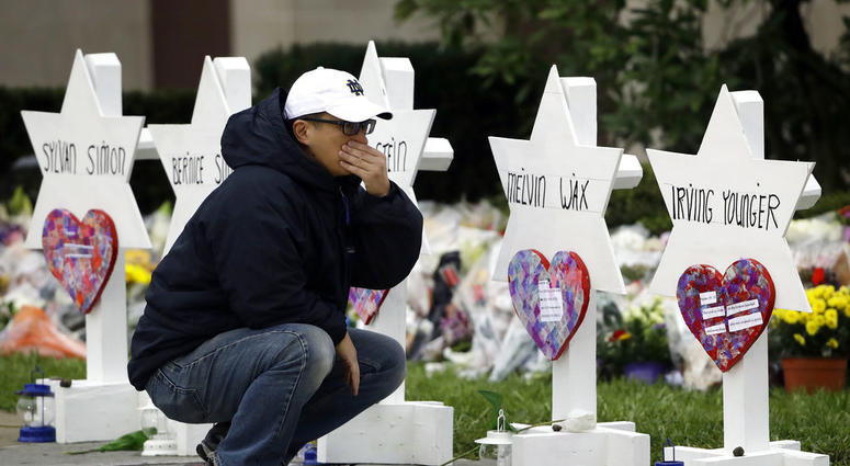 A person pauses in front of Stars of David with the names of those killed in a deadly shooting at the Tree of Life Synagogue, in Pittsburgh, Monday, Oct. 29, 2018.