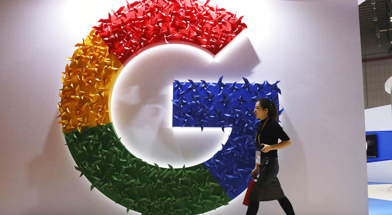 In this Monday, Nov. 5, 2018, photo, a woman carries a fire extinguisher past the logo for Google at the China International Import Expo in Shanghai.